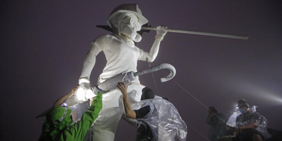 """Manifestantes antigubernamentales cargan la estatua """"Lady Liberty"""" para colocarla en una montaña emblemática de Hong Kong, el """"Lion Rock"""". (REUTERS / Tyrone Siu)."""