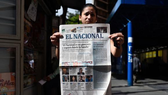 En esta foto de archivo tomada el 14 de diciembre de 2018, una mujer muestra la última edición impresa del diario venezolano El Nacional en Caracas. (Federico PARRA / AFP).