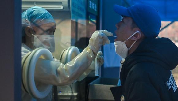 Un trabajador de la salud toma una muestra de un hisopo de un hombre para realizar una prueba del coronavirus en un hospital en Wuhan, provincia central de Hubei en China, el 7 de febrero de 2021. (Hector RETAMAL / AFP).
