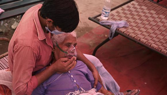 Un familiar consuela a una paciente que respira con la ayuda del oxígeno proporcionado por un Gurdwara, un lugar de culto para los sijs, debajo de una carpa instalada a lo largo de la carretera en medio de la pandemia del coronavirus en la India. (Foto de Tauseef). MUSTAFA / AFP).