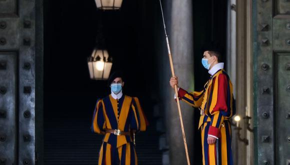 Guardias suizos con mascarillas por el coronavirus montan guardia junto a la Puerta de Bronce en el Vaticano, el 13 de octubre de 2020. (AFP / Andreas SOLARO).