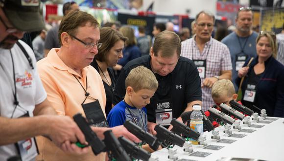 La gente busca armas de fuego en una sala de exposiciones en la convención anual de la NRA el sábado 5 de mayo de 2018 en Dallas, Texas. (Foto de Loren ELLIOTT / AFP)