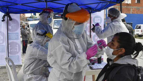 Un trabajador de salud toma una muestra de hisopo de una mujer para realizar una prueba de COVID-19 en Tranca de Urujara, La Paz, el 13 de febrero de 2021. (Foto: AFP / AIZAR RALDES).