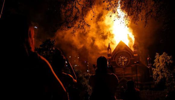 Un grupo de manifestantes observa como arde la iglesia de San Francisco de Borja, actualmente destinada al servicio religioso de Carabineros de Chile, este domingo durante una manifestación en los alrededores de la Plaza Italia de Santiago (Chile). (Foto: EFE/Stringer).