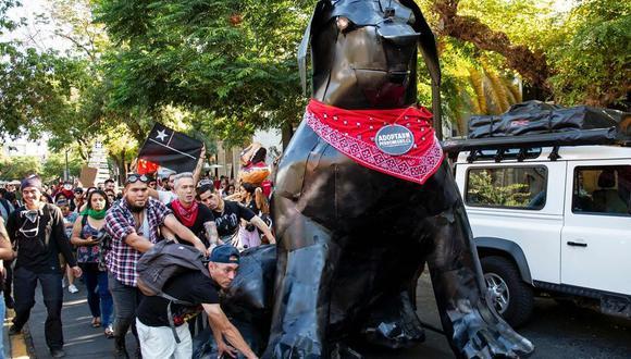 Los activistas llevan una escultura de metal del llamado perro Negro Matapacos en Santiago el 20 de diciembre del 2019. (AFP / Martin BERNETTI).