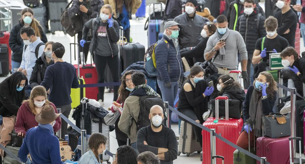 Passengers wear face masks to fend off coronavirus as they wait in line to check in for their flights, Tuesday, March 24, 2020, at JFK airport in New York. (AP Photo/Mary Altaffer)