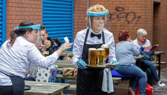 En esta foto de archivo tomada el 3 de julio de 2020, trabajadores que usan protectores faciales y guantes sirven cerveza en el centro de la ciudad de Belfast, tras la reapertura de los bares que estuvieron cerrados por el coronavirus. (Foto de Paul Faith / AFP).