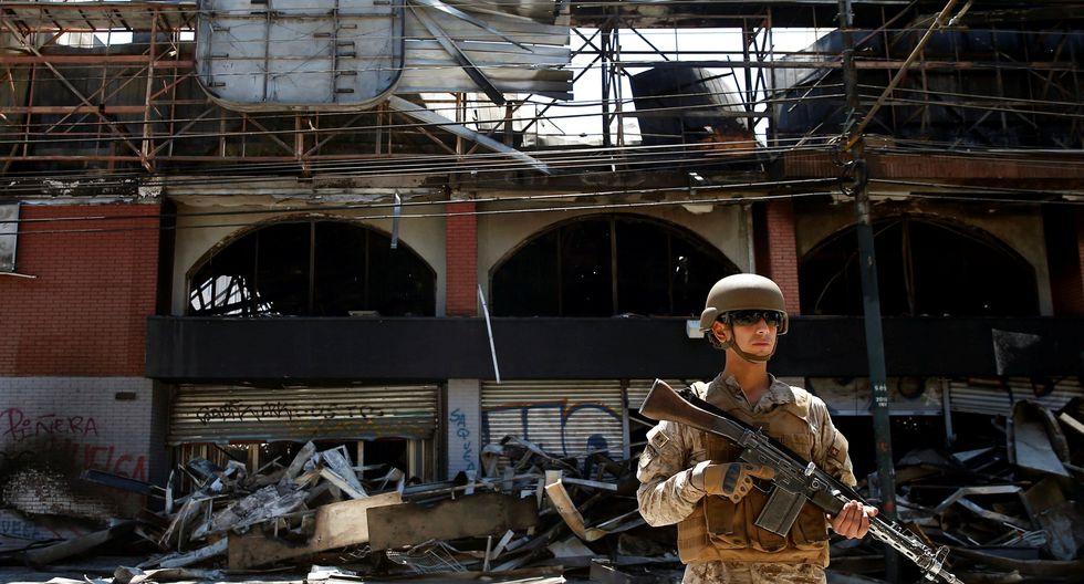 Un soldado resguarda un supermercado que fue saqueado y quemado en Valparaíso. (REUTERS/Rodrigo Garrido).