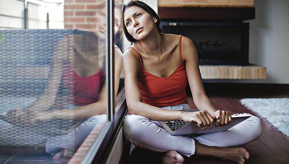 Latina woman between 23 and 29 years old, sitting on the floor of her house, with the computer on her legs, in nostalgic attitude, looking straight ahead