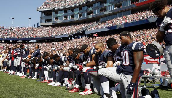 Jugadores de los Patriots de Nueva Inglaterra hincan la rodilla en el suelo durante el himno a modo de protesta por la brutalidad policial. (AP)