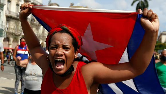 Una mujer manifiesta su apoyo al gobierno de Cuba en una calle en La Habana mientras cientos de cubanos protestan contra el régimen también en la capital. (EFE/Ernesto Mastrascusa).