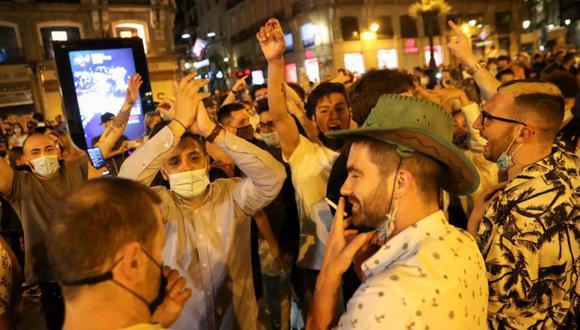 La gente celebra cuando se levanta el estado de emergencia decretado por el gobierno español para prevenir la propagación de la enfermedad del coronavirus (COVID-19) en la plaza Puerta del Sol en Madrid, España. (Foto: REUTERS / Susana Vera).