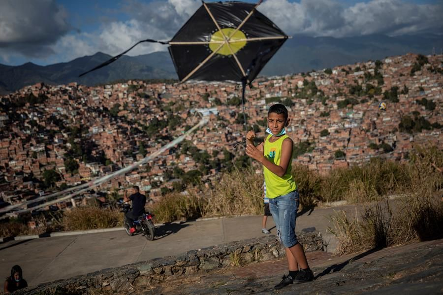 A boy lifts a parrot (kite) in Petare. (EFE / RAYNER PEÑA R).