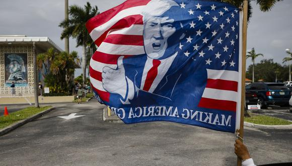 Un partidario sostiene una bandera que representa el rostro del presidente de Estados Unidos, Donald Trump, afuera de la Biblioteca Pública John F.Kennedy, mientras los votantes emiten sus primeras boletas en Hialeah, Florida. (Foto de Eva Marie UZCATEGUI / AFP).