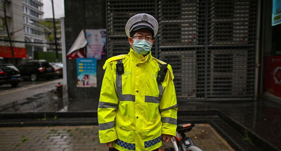 Un oficial de policía auxiliar, vestido con una máscara, observa en Wuhan, la provincia central de Hubei, en China, un día después de que las restricciones de viaje a la ciudad se aliviaron después de dos meses de cierre debido al brote de coronavirus. (Foto: AFP/Héctor Retamal)