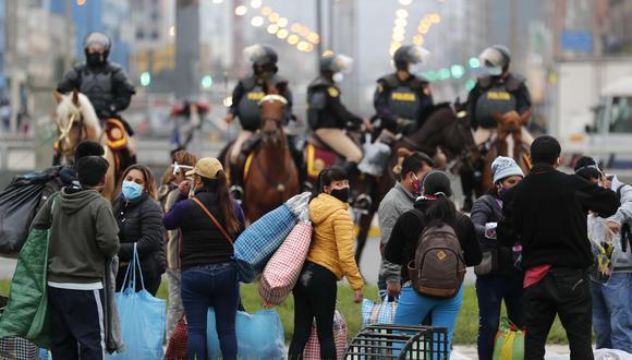 La posibilidad de desplazarse los domingos tiene limitaciones. En la imagen, vendedores ambulantes se desplazan luego de ser desalojados por la Policía de una vía pública donde trabajaban en el Centro de Lima. (Foto: Paolo Aguilar / EFE)