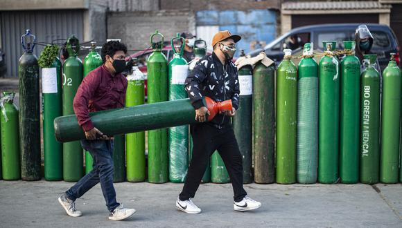 Jóvenes cargan un balón de oxígeno en el Callao. (Foto: ERNESTO BENAVIDES / AFP)