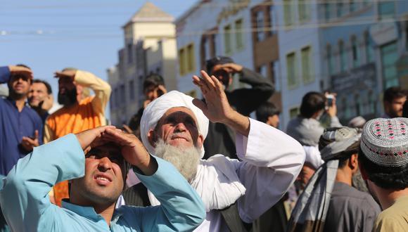 Afganos miran los cuerpos que los talibanes colgaron en la plaza de Herat. AP