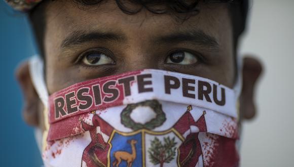"""John Sanchez, que usa una máscara facial con un mensaje que dice """"Resiste Perú"""", espera en la fila para hacerse la prueba de COVID-19 en el Hospital Almenara en Lima. (Foto AP / Rodrigo Abd)."""