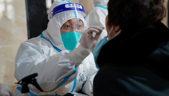 Un trabajador médico toma una muestra a un hombre mientras realiza un test de COVID-19 en un edificio de oficinas en Harbin, en la provincia de Heilongjiang, en el noreste de China. (STR / AFP)
