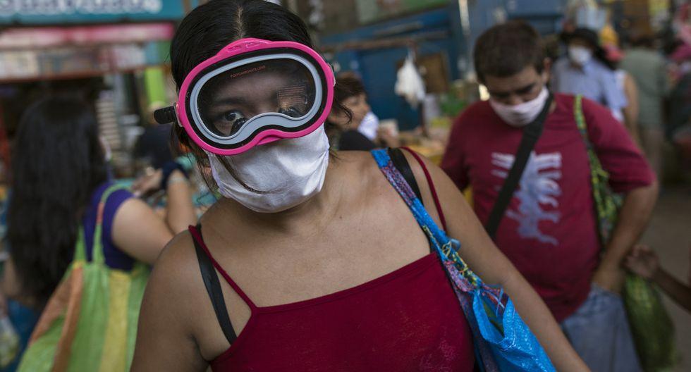 Una mujer usa una máscara de buceo y una máscara quirúrgica como medida de precaución contra la propagación del nuevo coronavirus. (AP Photo/Rodrigo Abd)