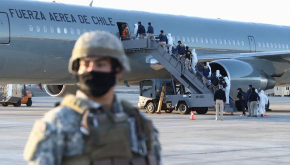 Migrantes venezolanos abordan un avión mientras son deportados luego de cruzar ilegalmente por la frontera entre Bolivia y Chile. (Foto de IGNACIO MUNOZ / AFP).