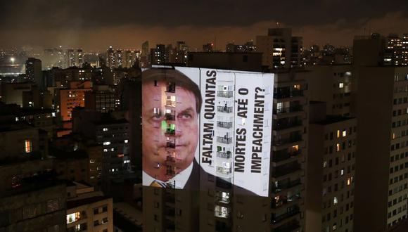 """Una imagen del presidente de Brasil, Jair Bolsonaro, con la frase """"Cuántas muertes hasta el juicio político"""", se proyecta en un edificio durante una protesta por sus políticas contra el coronavirus. (REUTERS / Amanda Perobelli)."""