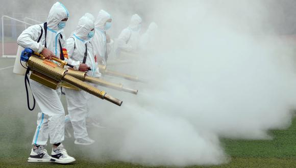Trabajadores rocían desinfectante en una escuela antes del nuevo semestre en Bozhou, en la provincia de Anhui, en el este de China, el 23 de agosto de 2021. (STR / AFP).