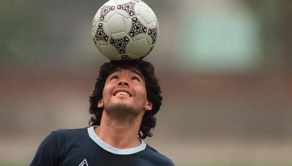 (FILES) In this file photo taken on May 22, 1986 Argentine football star Diego Maradona, wearing a diamond earring, balances a soccer ball on his head as he walks off the practice field following the national selection's practice session in Mexico City. - Argentinian football legend Diego Maradona passed away on November 25, 2020. (Photo by JORGE DURAN / AFP)