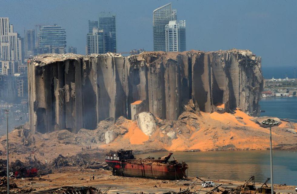 Una imagen tomada el 5 de agosto de 2020 muestra el silo de granos dañado y un barco quemado en el puerto de Beirut, un día después de que una poderosa explosión arrasara la capital del Líbano. (Foto por STR / AFP).
