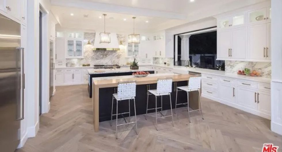 La cocina abierta da a una habitación familiar con puertas de vidrio que se abren al patio trasero, extendiendo el espacio exterior. (Foto: The MLS)