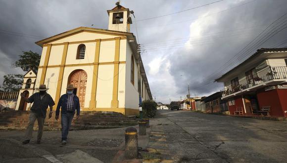 Hombres con máscaras para frenar la propagación del nuevo coronavirus caminan en Campohermoso, Colombia, el jueves 18 de marzo de 2021. Según el Ministerio de Salud, Campohermoso es uno de los dos municipios de Colombia que no ha tenido un solo caso de COVID-19 desde que comenzó la pandemia. (AP Foto/Fernando Vergara).