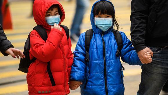 Imagen referencial. Niños con mascarillas cruzan una calle en Hong Kong, el pasado 27 de enero de 2020. (Anthony WALLACE / AFP).