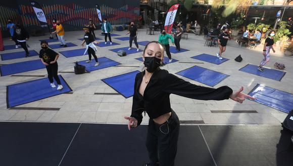 Jóvenes participan en una clase de baile al aire libre en el Centro Cultural Gabriela Mistral (GAM), el 22 de julio de 2021 en Santiago (CHILE). Los cines desempolvan sus butacas, los museos amplían su catálogo de actividades y los actores vuelven a los escenarios en la mayor parte de Chile, donde la pandemia remite y la cultura trata de resurgir tras más de un año contra las cuerdas por las duras restricciones. EFE/Elvis González