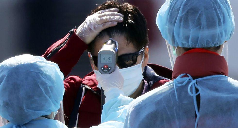 Un funcionario con su respectivo traje de protección mide la temperatura de los pasajeros extranjeros que bajan del crucero Diamond Princess. (AP).