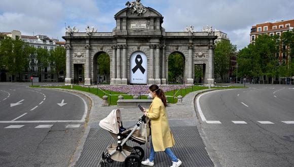 En esta foto de archivo tomada el 26 de abril de 2020, una mujer empuja un cochecito frente al monumento Puerta de Alcalá con una cinta negra para las víctimas del coronavirus Covid-19 en España. (Foto de Gabriel BOUYS / AFP).