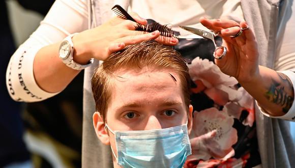 Una peluquera corta el cabello de un cliente tras la reapertura de actividades económicas en Berlín en medio de la pandemia de coronavirus. (Foto: AFP / Tobias Schwarz).