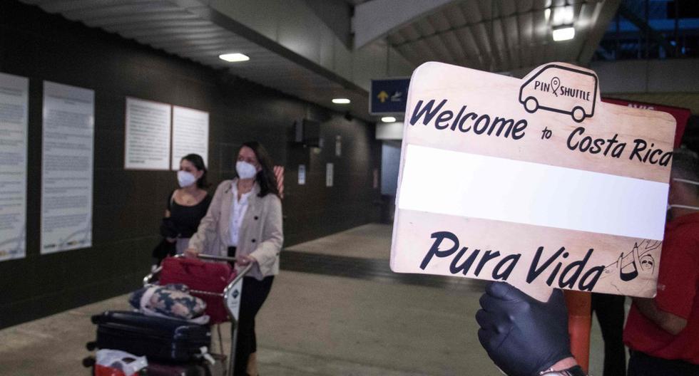 """Las personas llegan al aeropuerto Juan Santamaría, donde son recibidas por un operador turístico con un letrero que dice """"Bienvenido a Costa Rica, Pura Vida"""" en San José, el 3 de agosto de 2020. Se trata del primer vuelo comercial que aterriza en el país desde el inicio de la pandemia del coronavirus. (AFP / Ezequiel BECERRA)."""