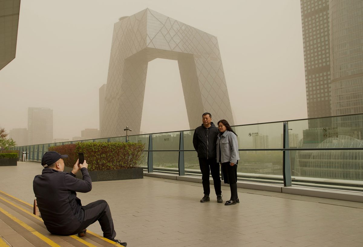 A couple pose for a photo outside the headquarters of China Central Television (CCTV). (Photo by Noel Celis / AFP).