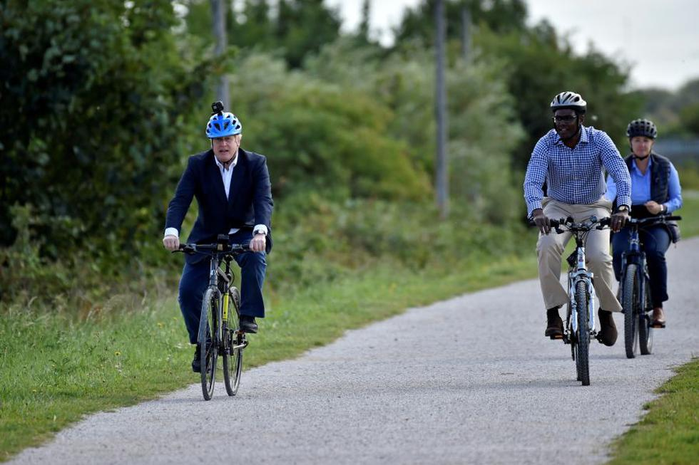 Boris Johnson (izq.) y el diputado conservador por Broxtowe Darren Henry manejan bicicleta en el Canal en Beeston, centro de Inglaterra. (Foto: Rui Vieira / POOL / AFP).