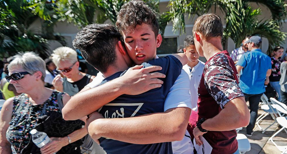 Dylan O'Neill, 15, facing, hugs James Bolger, 16, both students from Marjory Stoneman Douglas High School at the conclusion of a vigil at the Parkland Baptist Church, for the victims of the Wednesday shooting at the school, in Parkland, Fla., Thursday, Feb. 15, 2018. Nikolas Cruz, a former student, was charged with 17 counts of premeditated murder on Thursday. (AP Photo/Gerald Herbert)