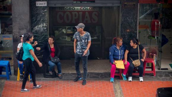 Estos tramitadores se ubican frente al edificio del SAT y llaman clientes  para abogados, entre ellos, Carlos de la Cruz. (El Comercio)