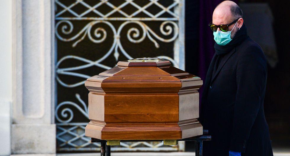 Un hombre con una máscara facial mira el ataúd de su madre durante un funeral en el cementerio cerrado de Seriate, cerca de Bérgamo, Lombardía, la región de Italia más golpeada por el coronavirus. (AFP / Piero Cruciatti).