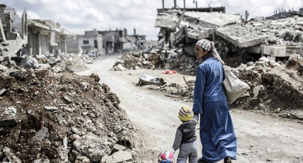 En esta foto de archivo tomada el 25 de marzo del 2015, una mujer kurda siria camina con su hijo frente a las ruinas de la ciudad de Kobane. (Foto de YASIN AKGUL / AFP).