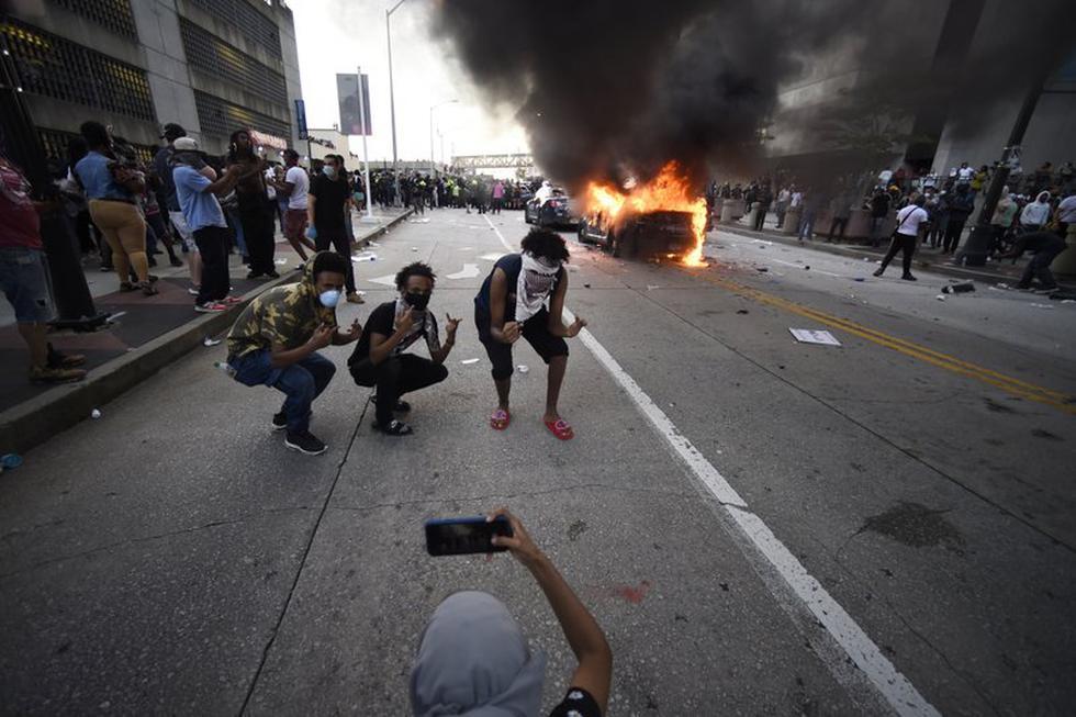 Un carro del Departamento de Policía de Atlanta arde mientras tres personas posan para una fotografía durante una manifestación contra la violencia policial. (AP Foto/Mike Stewart).