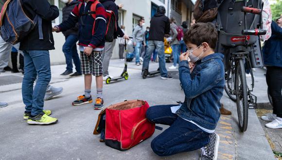 Un niño se ajusta la máscara protectora antes de ingresar a su escuela primaria, en París, el 26 de abril de 2021, cuando las escuelas primarias y los jardines de infancia franceses reabren después de tres semanas de cierre. (Foto: Thomas SAMSON / AFP)