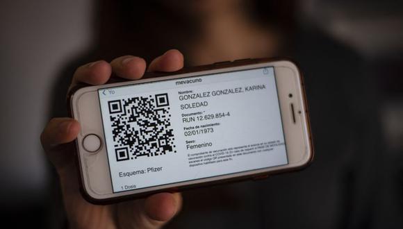 Una mujer muestra una tarjeta de movilidad en su teléfono celular que le permite moverse por Chile, incluso entre ciudades que están dentro y fuera de cuarentena en medio de la nueva pandemia del coronavirus COVID-19. (Foto de Martin BERNETTI / AFP).