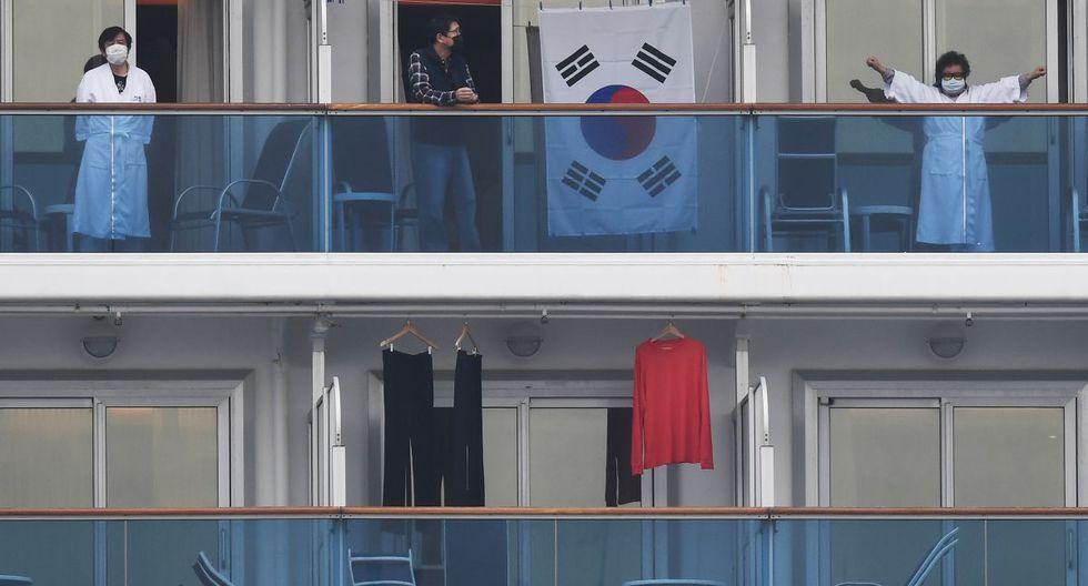Pasajeros del Diamond Princess miran el puerto de Yokohama desde sus balcones. (AFP)