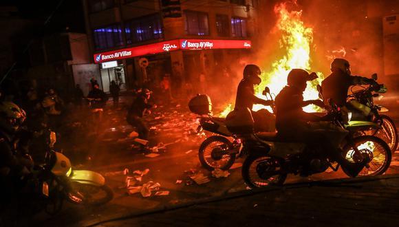 Manifestantes agrediendo a los policías motorizados de Bogotá. (Foto: AFP)