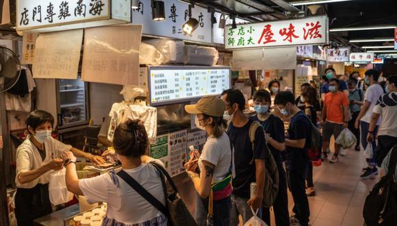 Los clientes que llevan máscaras protectoras hacen fila para pedir sus comidas para llevar en un restaurante en Sai Wan Ho de Hong Kong, China. (Foto: Roy Liu / Bloomberg).